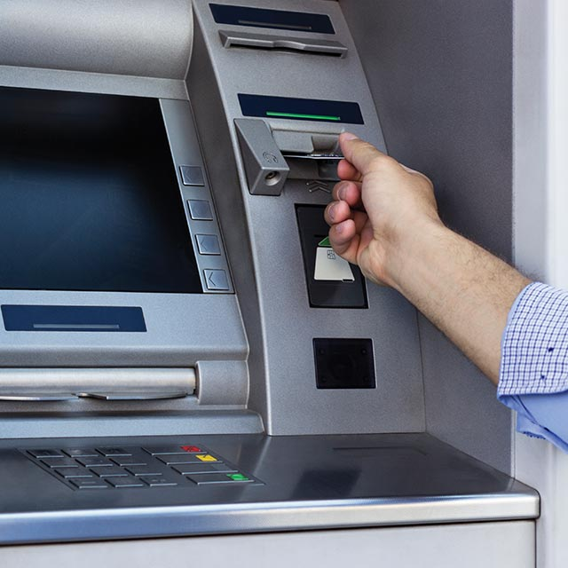 Men taking money out of ATM