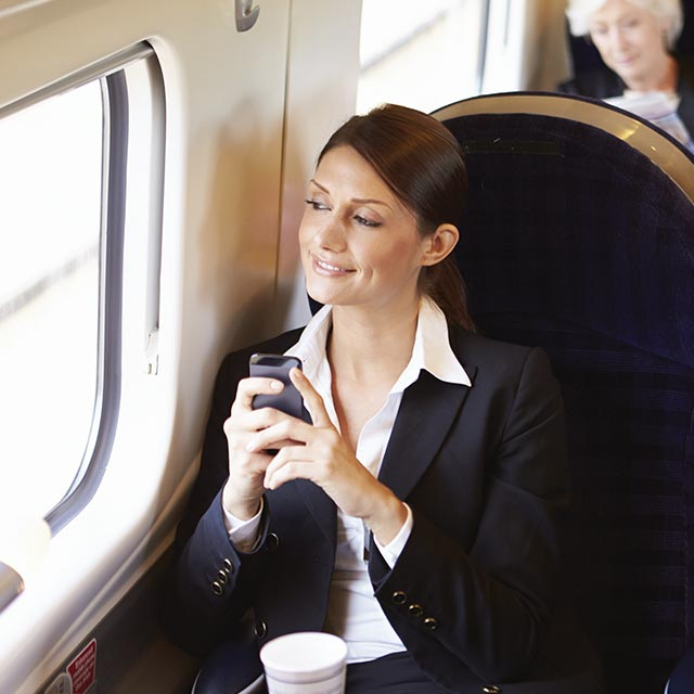 Women at train with cellphone